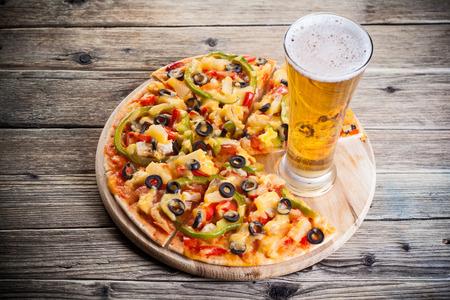 ピザとビールのガラス テーブルの上