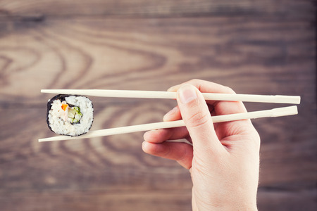 japanese meal: Hand holding sushi roll using chopsticks on wooden background