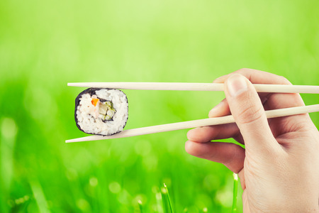 Hand holding sushi roll using chopsticks against green grass photo