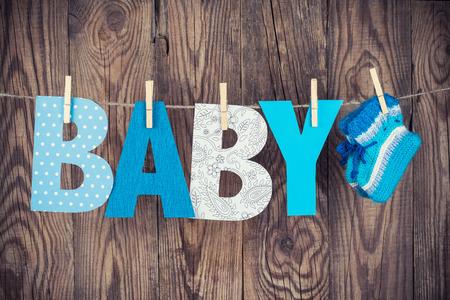 単語の赤ちゃんと掛かっている木製の背景に対して物干しニットの靴下の手紙