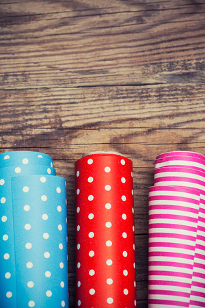 Rolls of colored wrapping paper on wooden background  photo