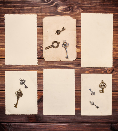 old paper sheets with vintage keys on wooden background photo