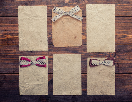 six old paper sheets with colorful bows on wooden background photo