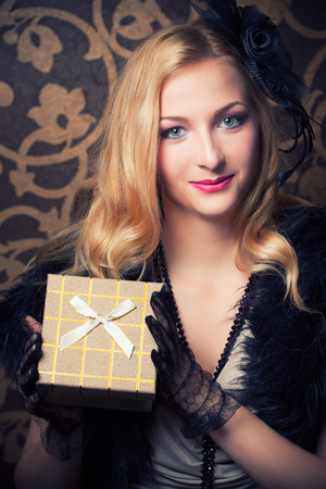 beautiful retro woman holding a golden gift box photo