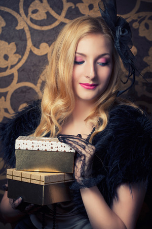 beautiful retro woman holding a golden gift box photo