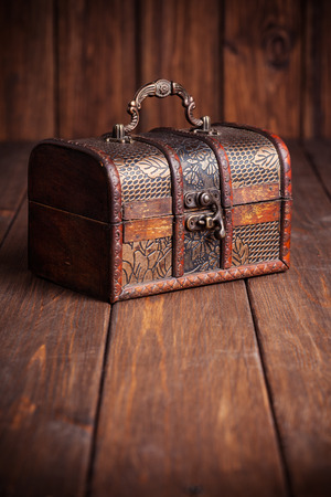 treasure box: closed treasure chest standing on wooden table