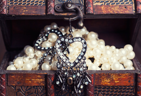 vintage earrings in a form of hearts hanging on old treasure chest photo