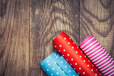wrapping paper: Rolls of colored wrapping paper on wooden background  Stock Photo