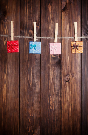 four small gift boxes hanging on clothesline against wooden background photo