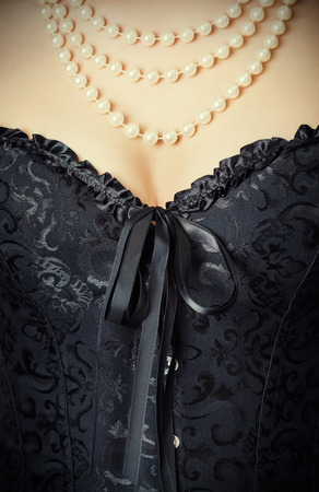 woman wearing black corset and pearls against retro background Фото со стока