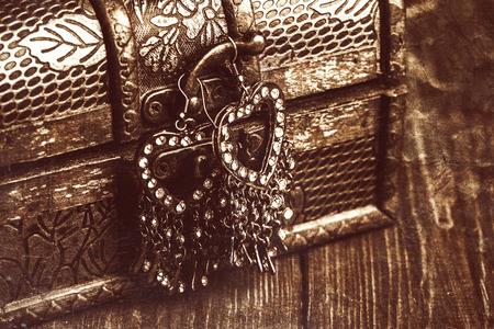 cofre tesoro: pendientes de la cosecha en una forma de corazones colgando de viejo cofre del tesoro Foto de archivo