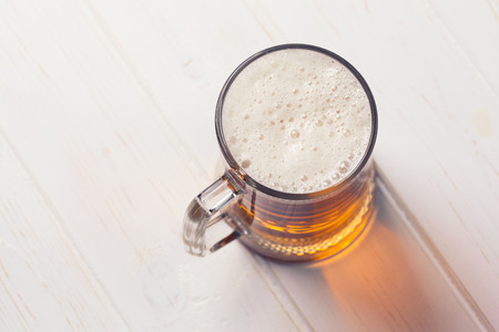 Mug of beer on wooden background  Imagens