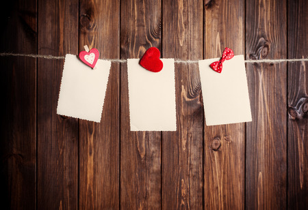 three old paper sheet with bow and hearts hanging on clothesline against wooden background photo