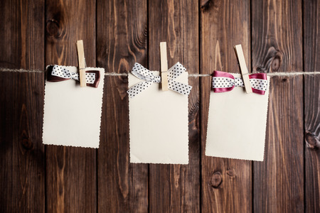 three old paper sheets with bows hanging on clothesline against wooden background photo