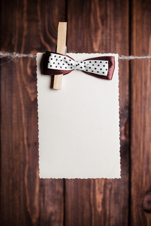 old paper sheet with bow hanging on clothesline against wooden background photo