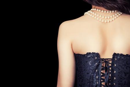 女性は黒のコルセットとクリッピング パスと黒の背景の真珠を着て