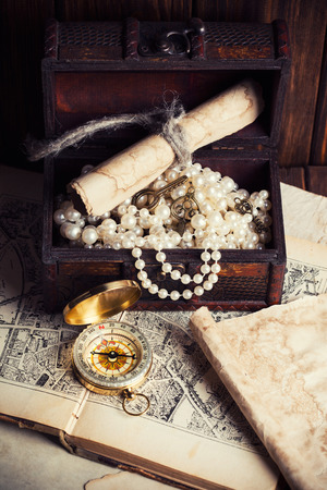 treasure chest, compass and old map on wooden table photo