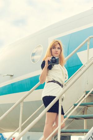 gangway: beautiful woman with vintage camera posing on plane gangway