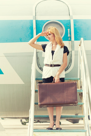 gangway: beautiful woman with old suitcase posing on plane gangway