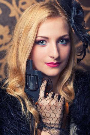 beautiful retro woman holding a revolver photo