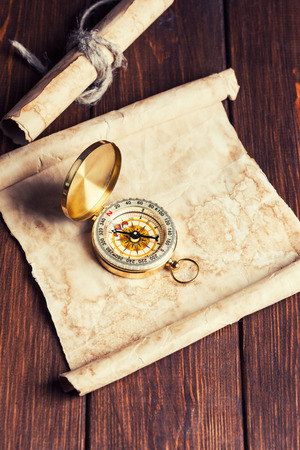 old unrolled map, rolled map and compass on wooden table photo