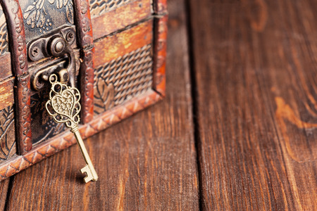 key box: vintage key and old treasure chest on wooden table