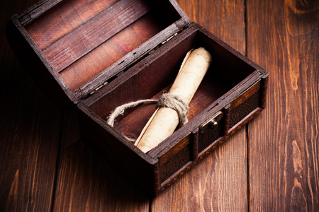 old paper roll inside treasure chest on wooden background Stock Photo