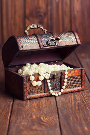 old treasure chest with pearl necklaces standing on wooden table photo
