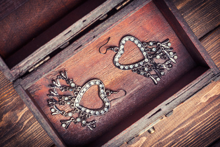 vintage earrings in a form of hearts inside old treasure chest photo