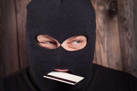 Hacker holding a credit card on wooden background photo