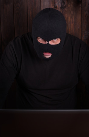 Hacker in a balaclava standing in the darkness furtively stealing data off a laptop computer on wooden background Stock Photo