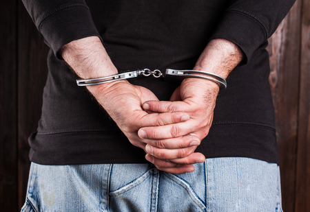 cuffed: man hands in handcuffs