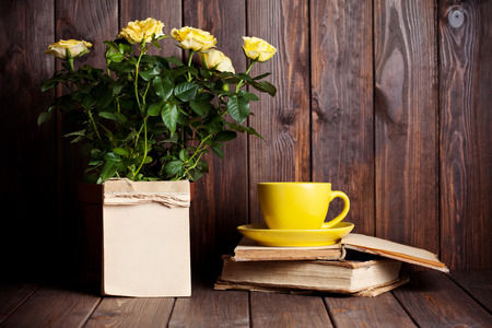 flower pot: yellow roses in pot, tea cup and old books on wooden table