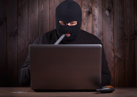 furtively: Hacker in a balaclava standing in the darkness furtively stealing data off a laptop computer on wooden background Stock Photo