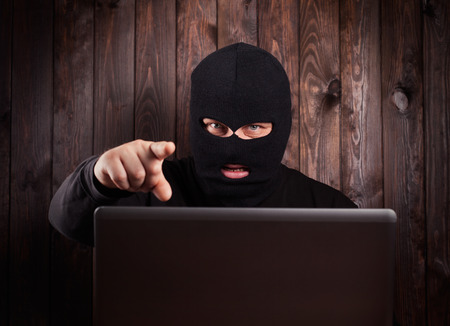 Hacker in a balaclava standing in the darkness furtively stealing data off a laptop computer on wooden background photo
