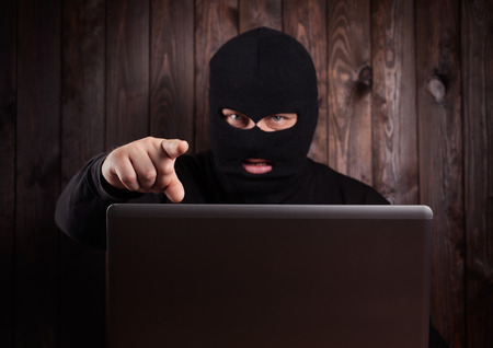 scammer: Hacker in a balaclava with focus on finger
