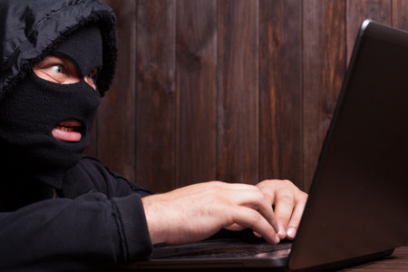 scammer: Hacker in a balaclava standing in the darkness furtively stealing data off a laptop computer on wooden background Stock Photo