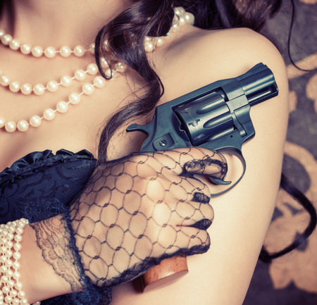 woman wearing black corset and pearls and holding a gun against retro background photo