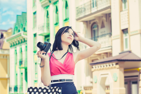 beautiful young woman taking photos with vintage camera on a city street photo