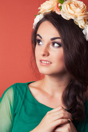 beautiful young woman wearing wreath against red background photo