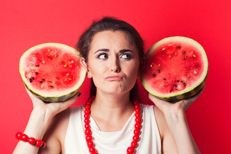 beautiful young woman holding watermelon against red background photo