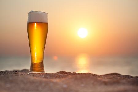 tomando alcohol: Vaso de cerveza en una puesta de sol