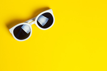 Stylish white sunglasses on yellow background