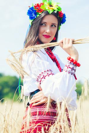 beautiful young woman wearing national ukrainian clothes posing in wheat field photo