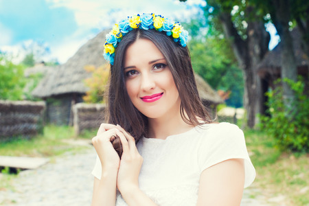 beautiful young woman wearing blue and yellow wreath and posing against old hut photo