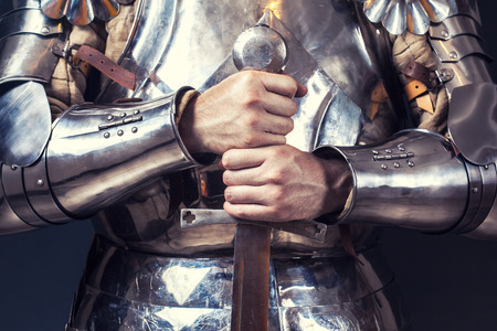 armour: knight wearing armor and holding two-handed sword Stock Photo