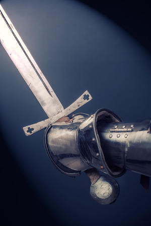 longsword: closeup of knights hand in armor gloves holding two-handed sword