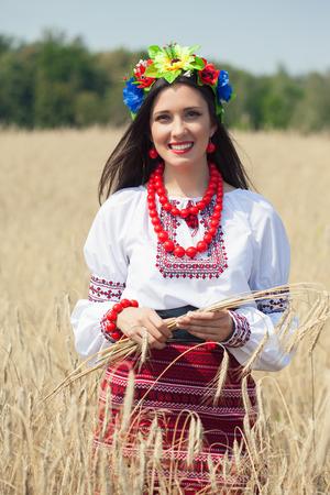 beautiful young woman wearing national ukrainian clothes posing in wheat field Фото со стока