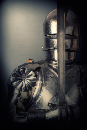 knight wearing armor and holding two-handed sword Фото со стока
