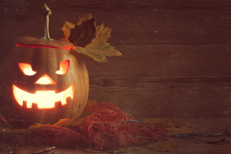 jack-o-lantern with leaves on wooden  photo